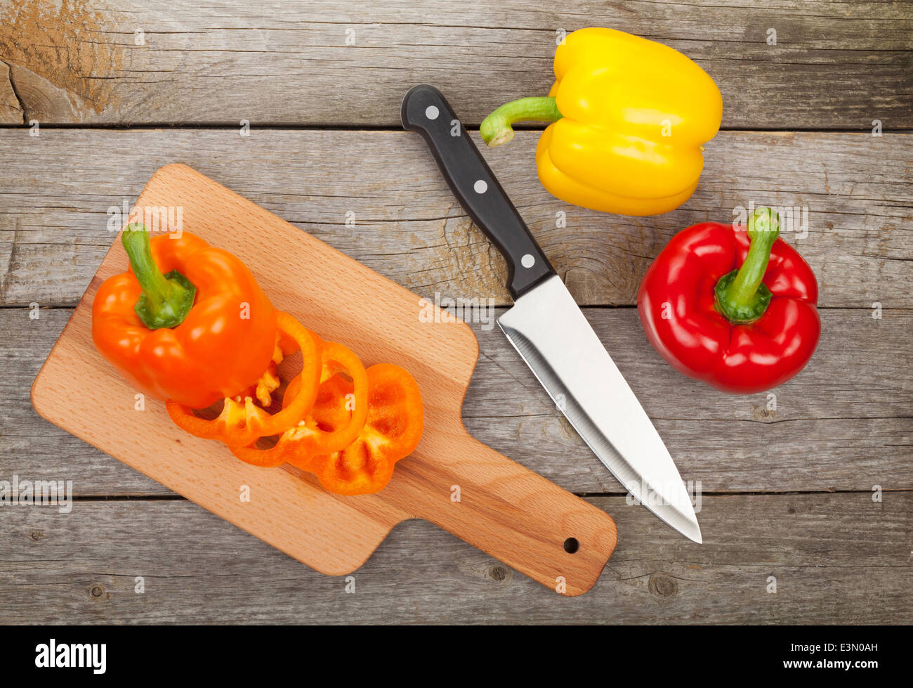 Colorful bell peppers and kitchen utensils over wooden table background - Stock Image