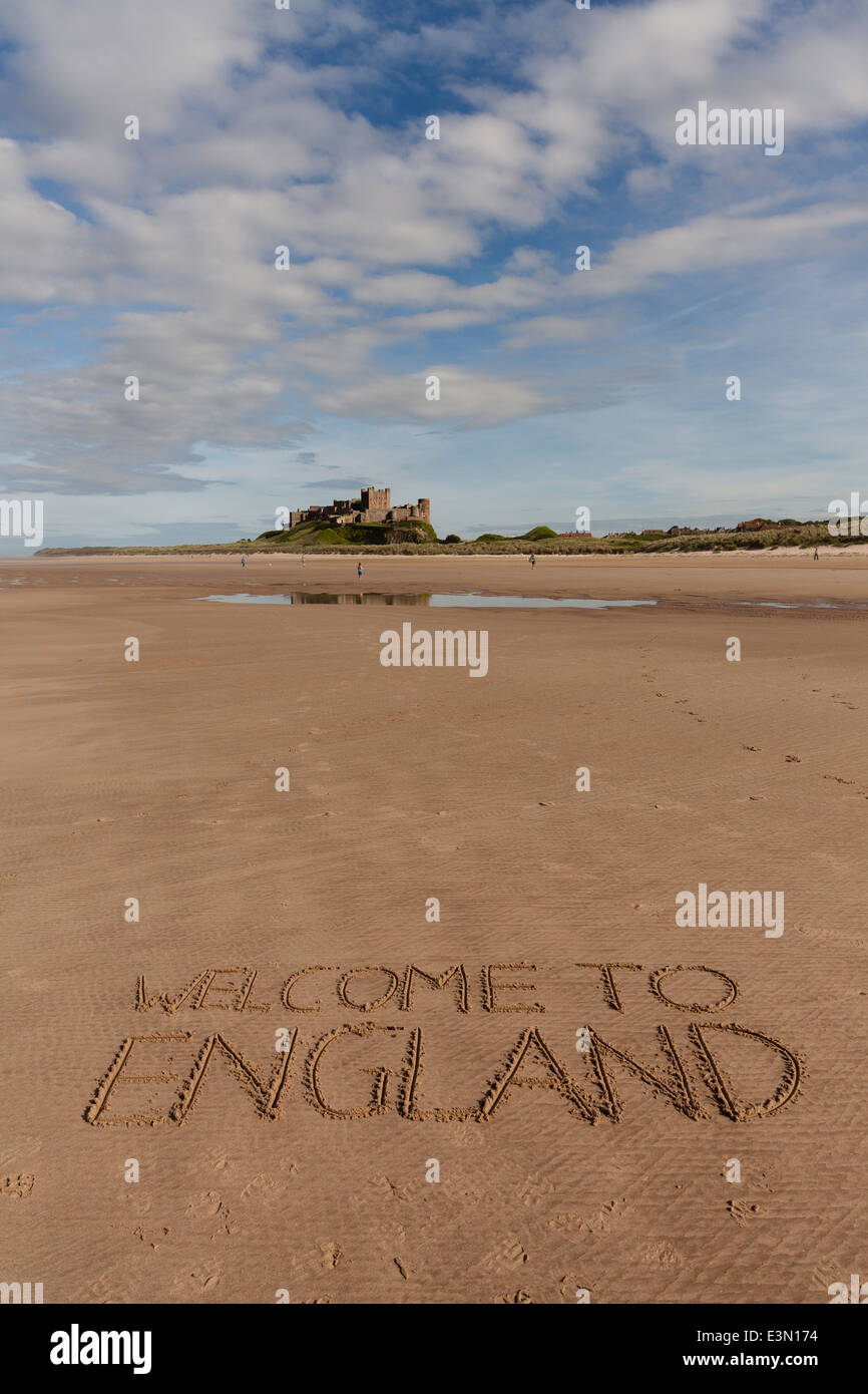 Welcome to England written in sand on beach at Bamburgh, UK with Bamburgh Castle in background - Stock Image