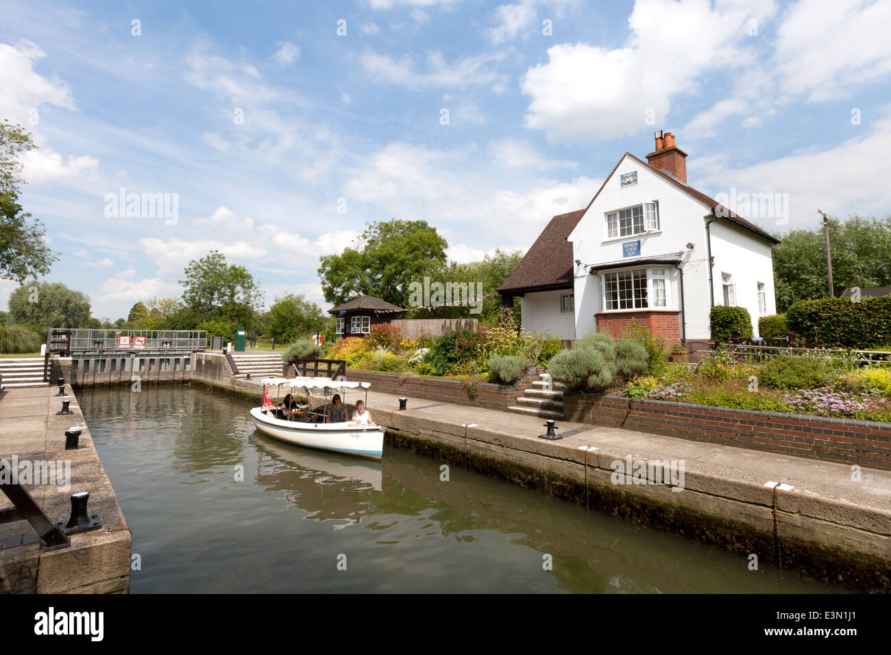 A boat in Benson Lock, with the lock house, River Thames, Oxfordshire, England UK Stock Photo