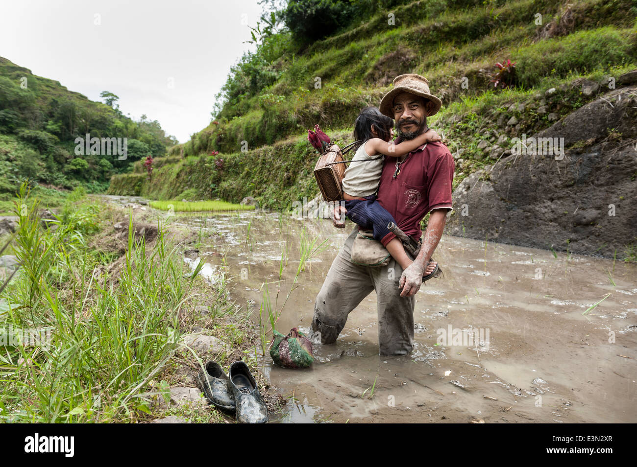 Man with his daughter in a ricefield, Luzon, Philippines. - Stock Image
