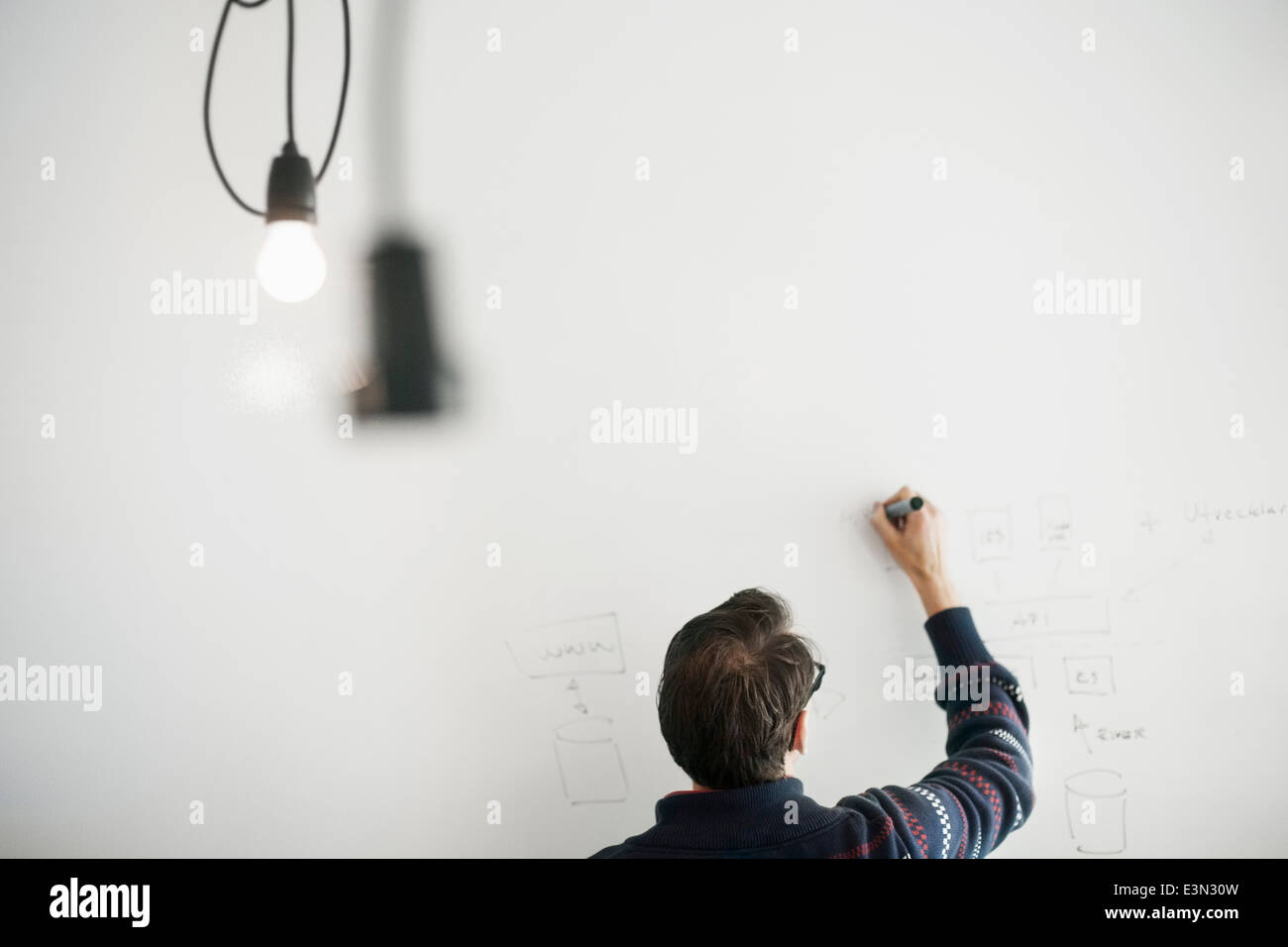 Rear view of businessman preparing strategy on whiteboard in office - Stock Image