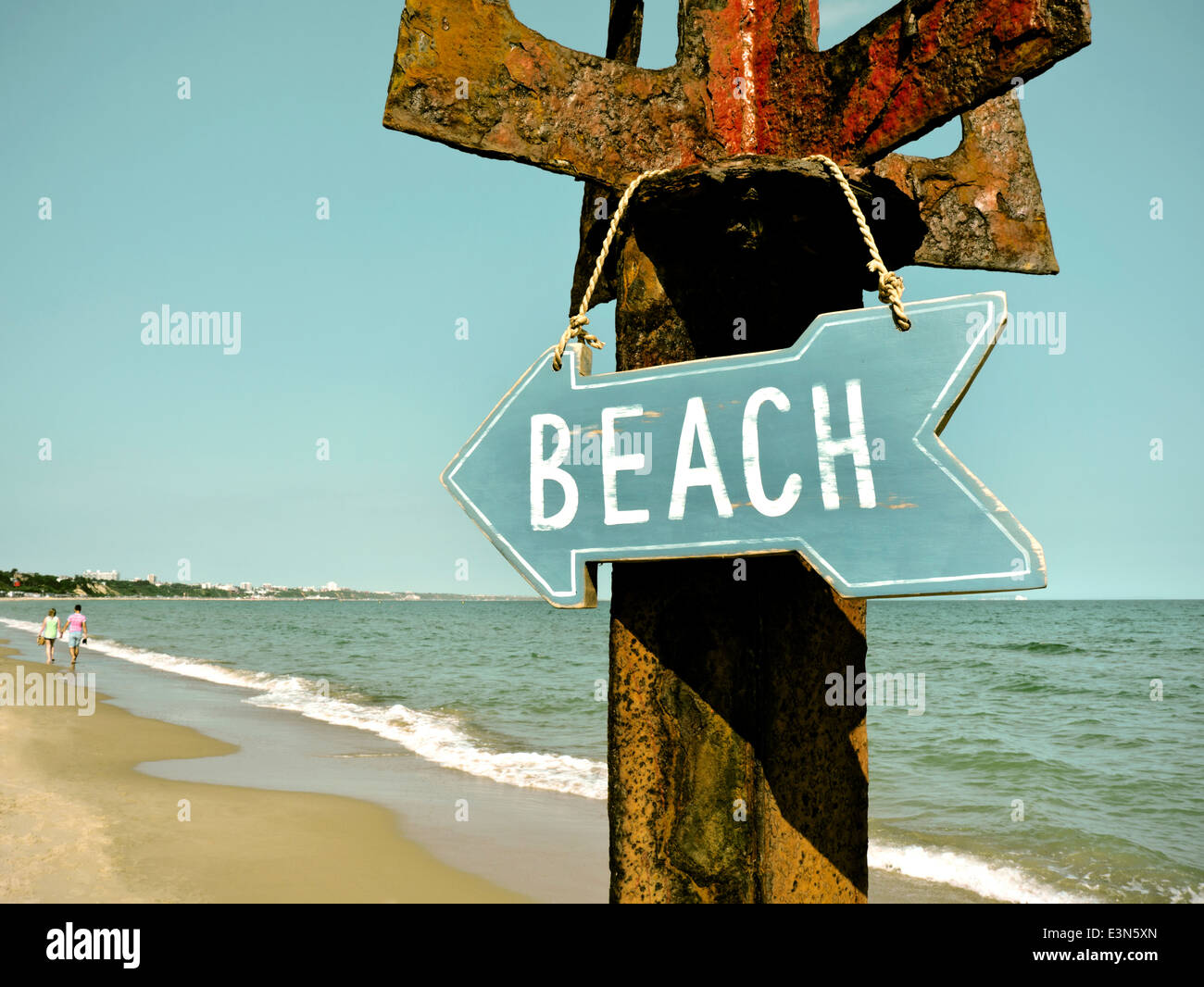 Retro concept 1950's 1960's film image treatment beach sign hanging on rustic post couple in background - Stock Image