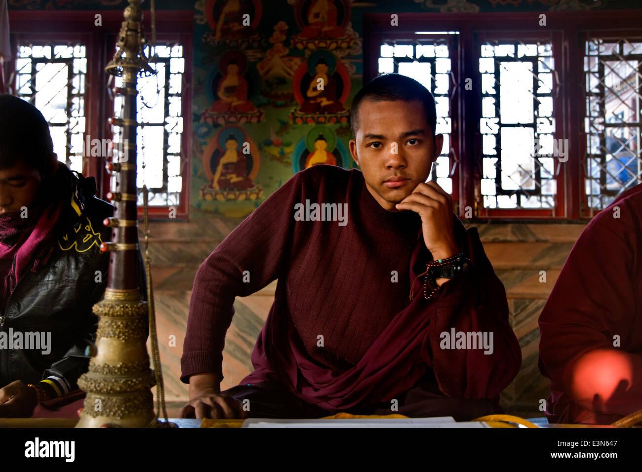 A Tibetan Buddhist MONK inside a monastery near BODHANATH STUPA - KATMANDU, NEPAL - Stock Image