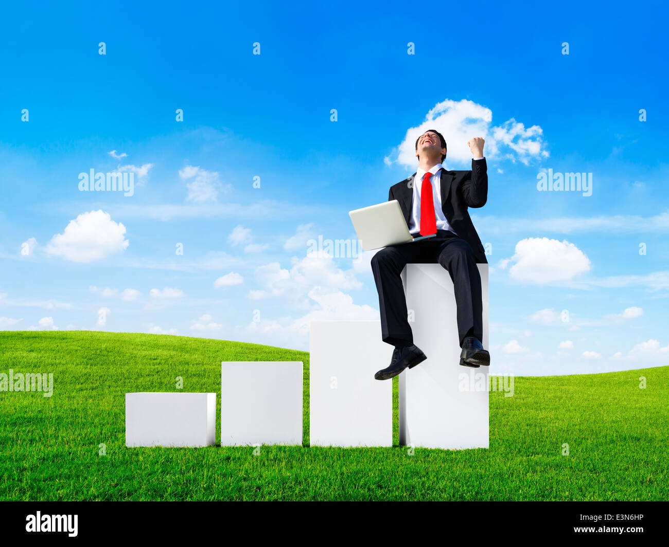 Business Man Outdoors Sitting on a Bar Graph Celebrating - Stock Image