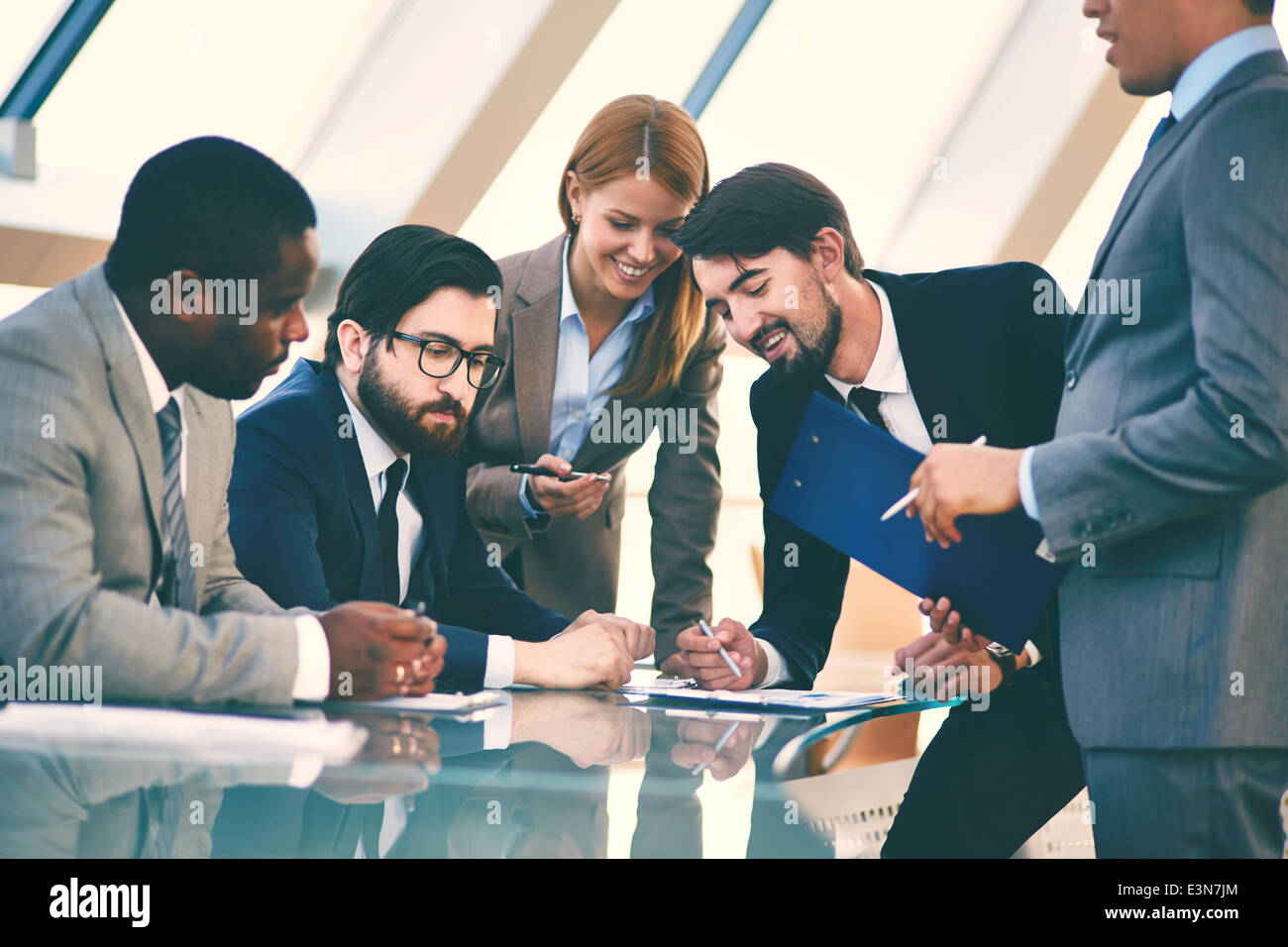 Group of business people discussing data or explaining ideas at meeting - Stock Image