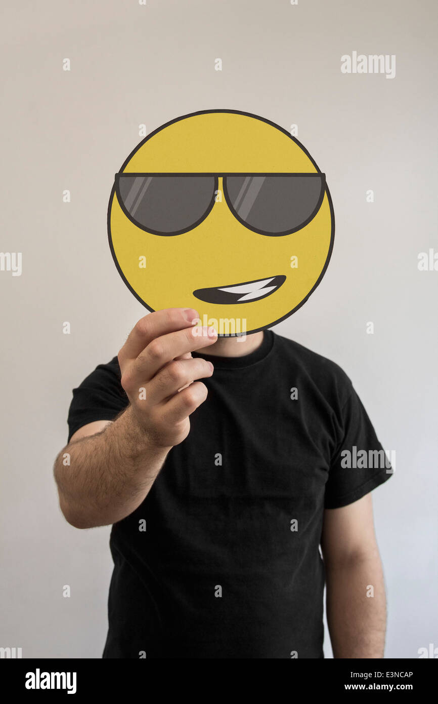 Man holding a cool, sunglass wearing emoticon face in front of his face - Stock Image