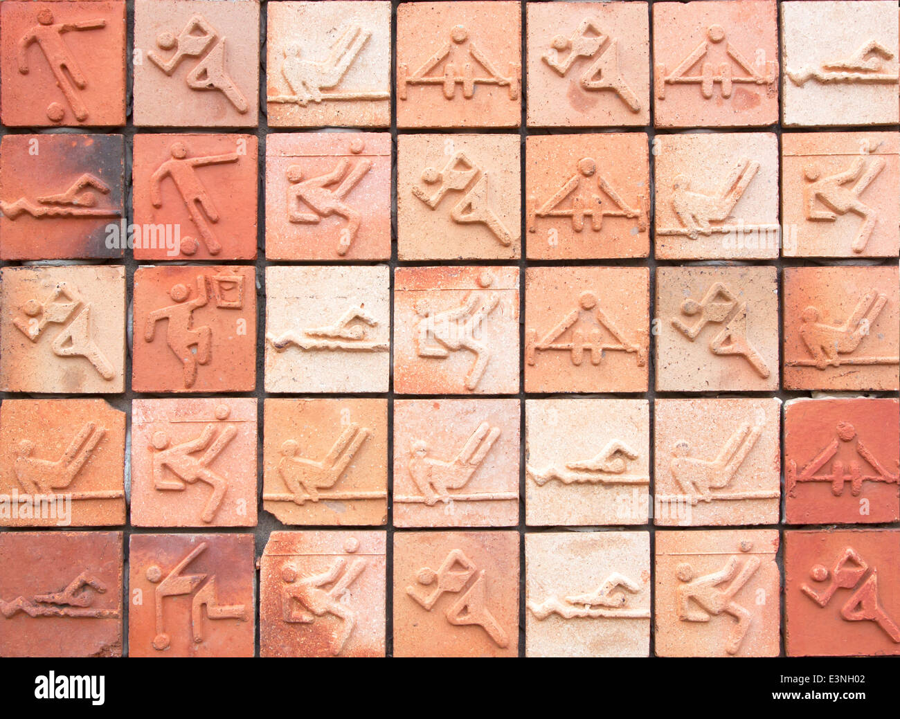 Wall tiles are shaped icon people exercise in various postures. - Stock Image