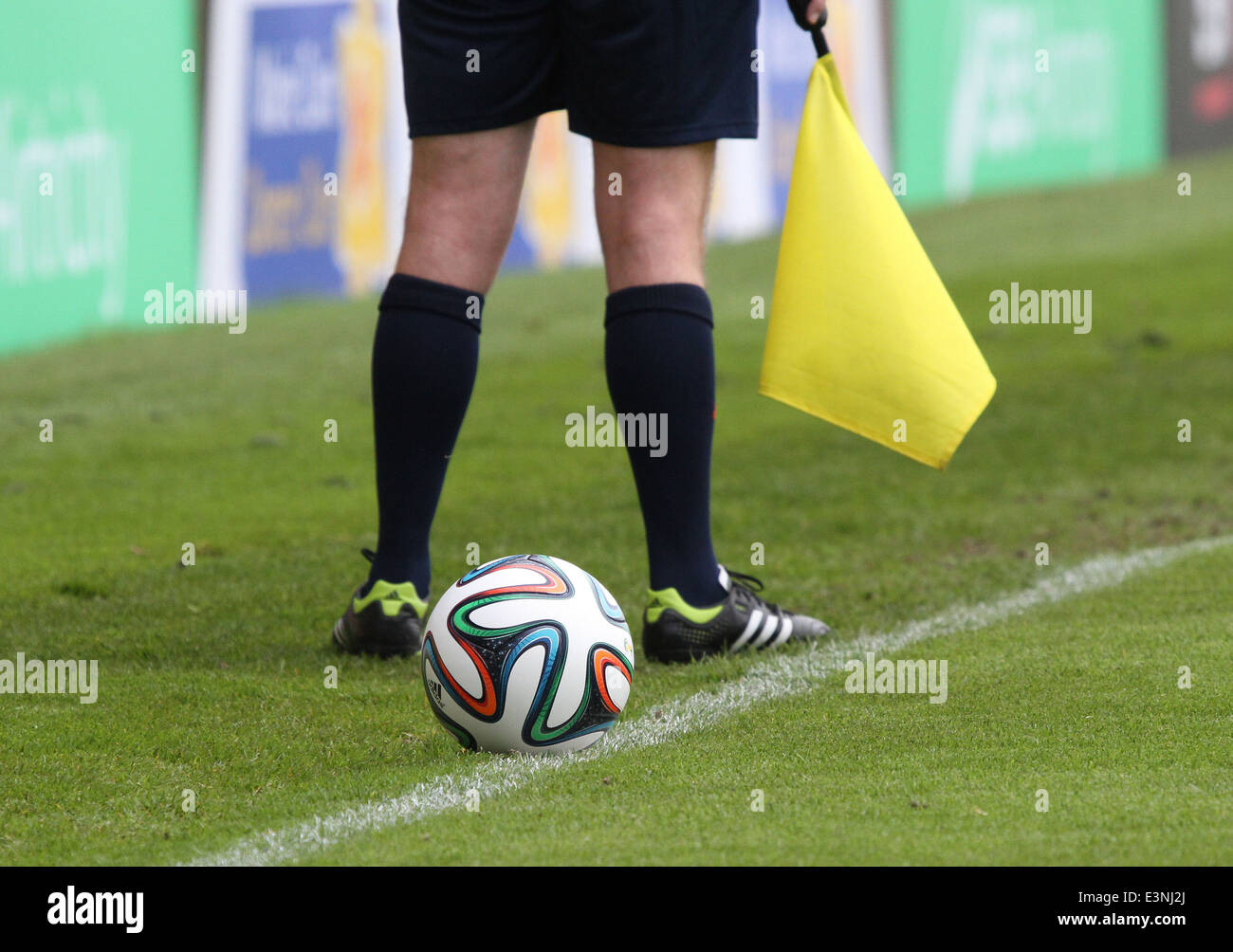 A football at side of pitch with referee's assistant behind it - Stock Image