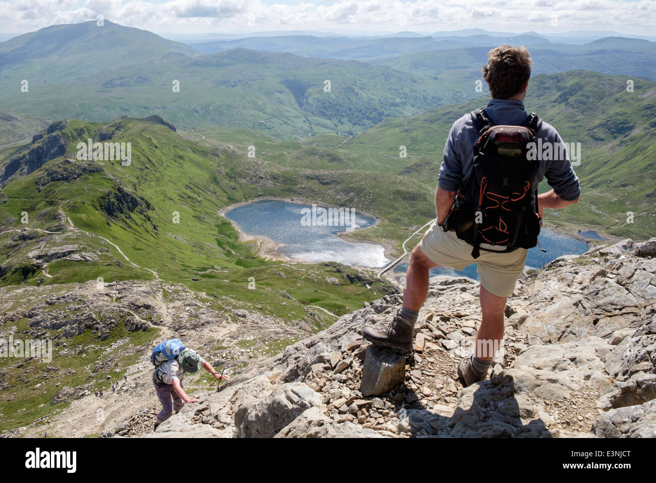 Hikers people scrambling up Crib Goch with view down at start of Snowdon Horseshoe in mountains of Snowdonia National - Stock Image