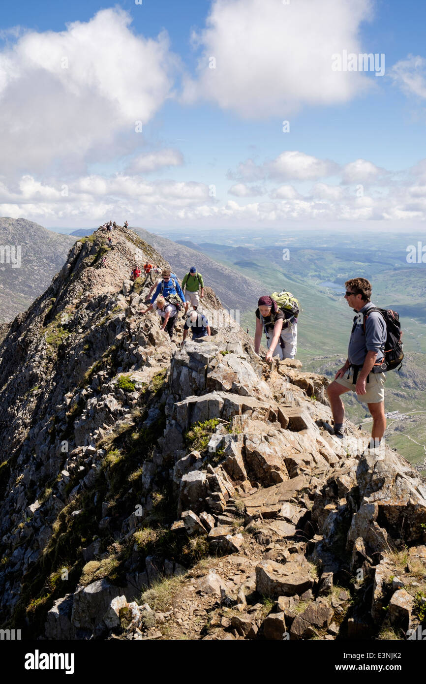 View back along Crib Goch ridge scramble with hikers scrambling at start of Snowdon Horseshoe in mountains of Snowdonia - Stock Image