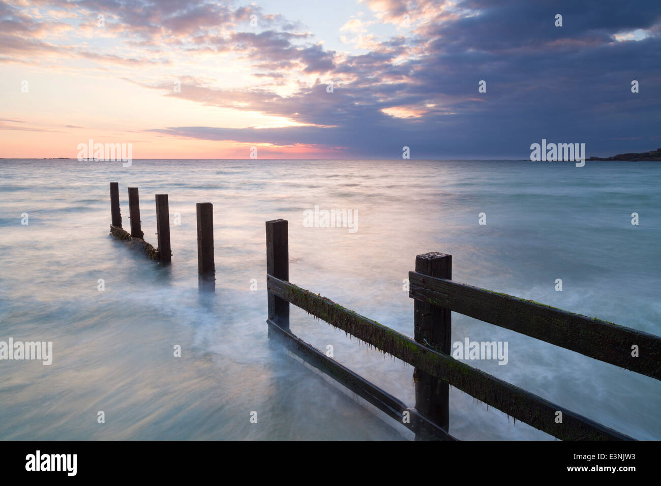 Wooden posts at sunset Vazon beach Guernsey - Stock Image
