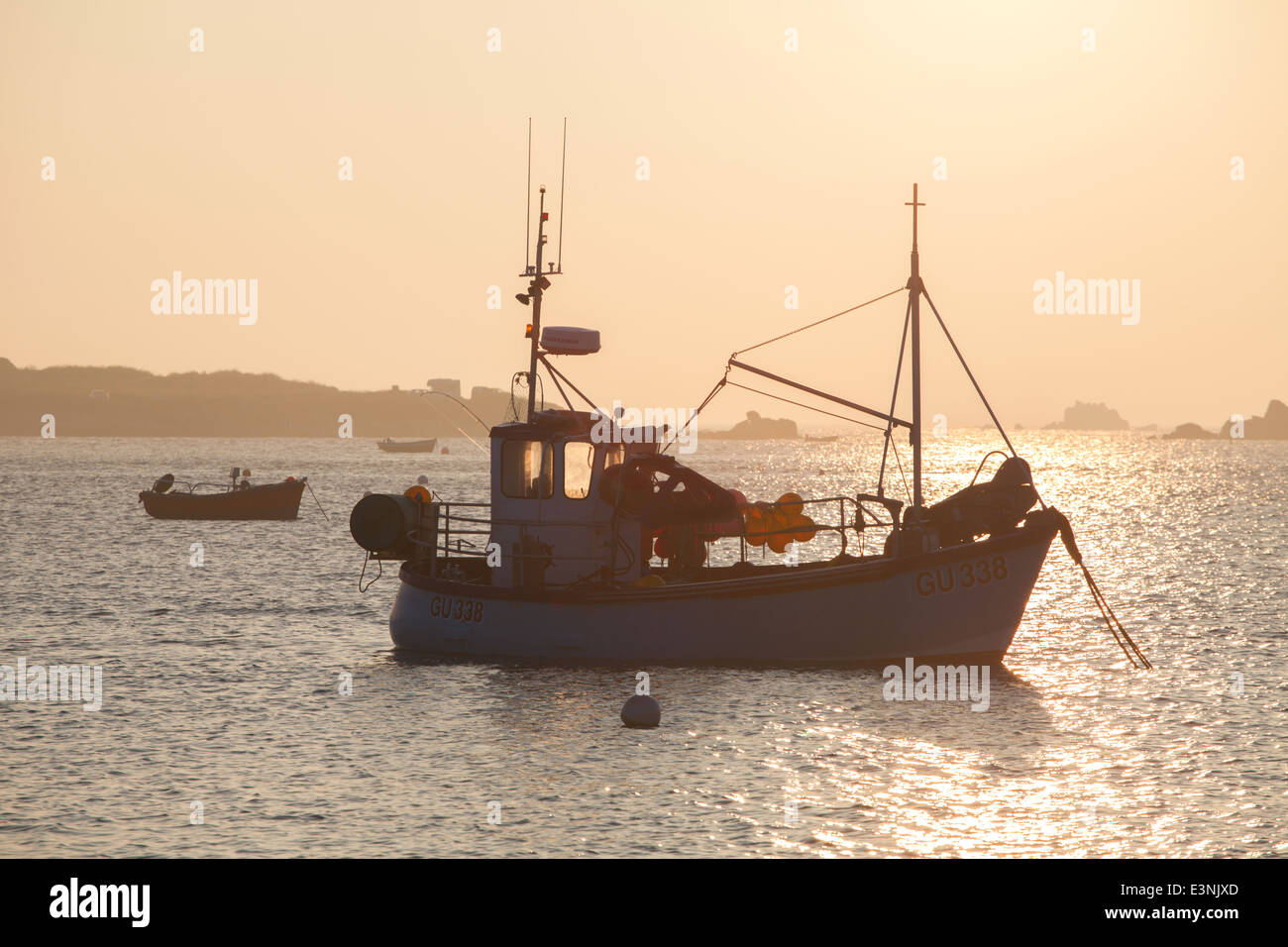 Sunset over fishing boat Le Grand Havre Guernsey - Stock Image