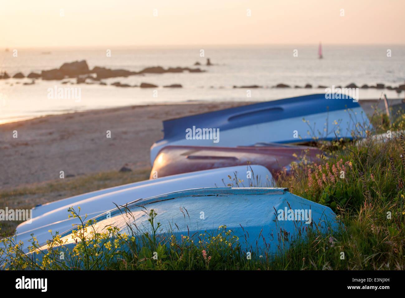 Golden sunlight on upturned boats Le Grand Havre Guernsey - Stock Image