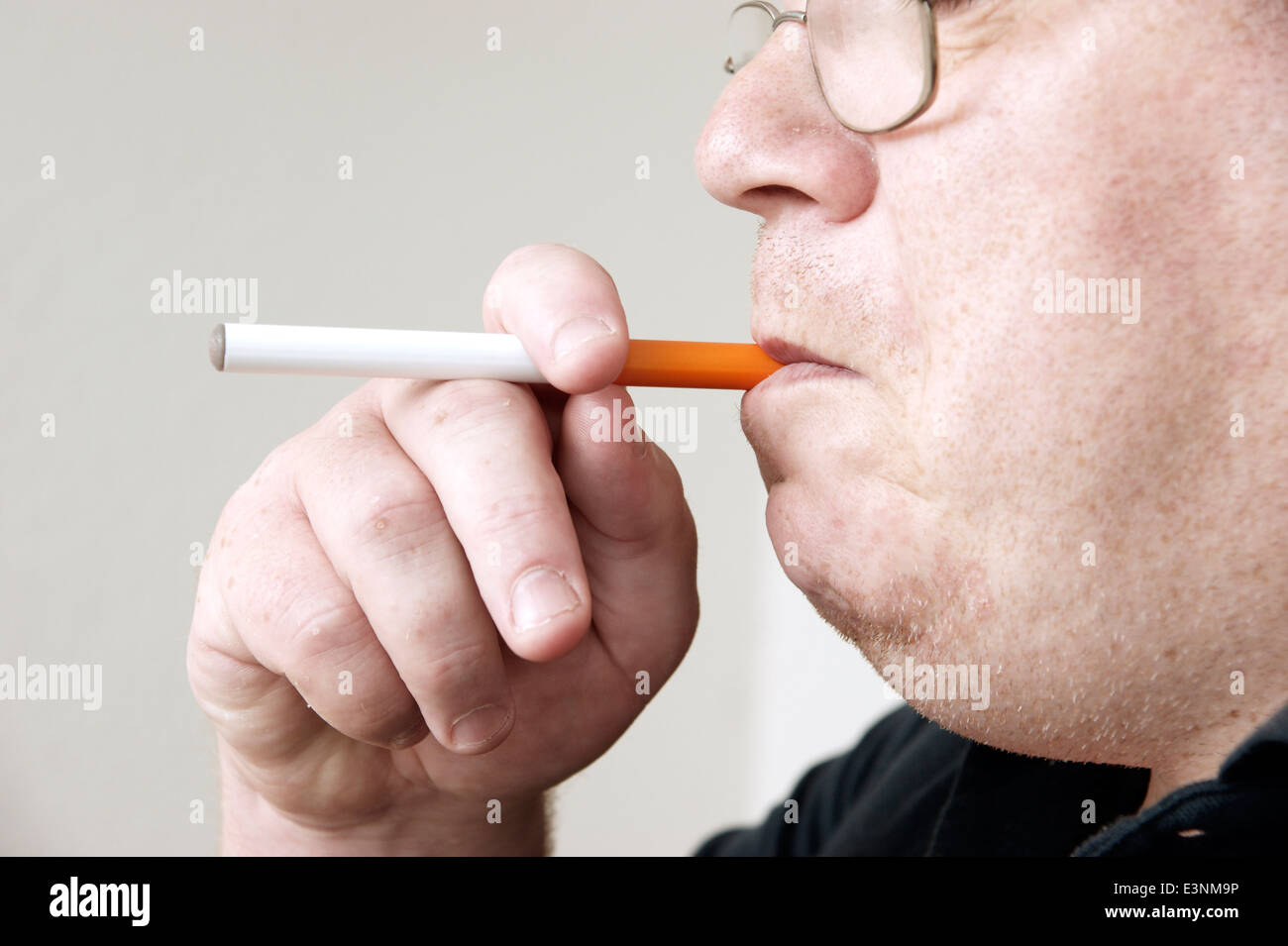 Man holding & smoking an electronic disposable E Cigarette (e-cigarette) - Stock Image