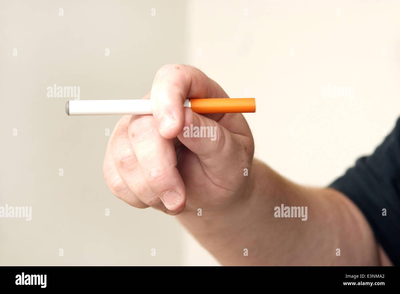Man holding an electronic disposable E Cigarette (e-cigarette) - Stock Image
