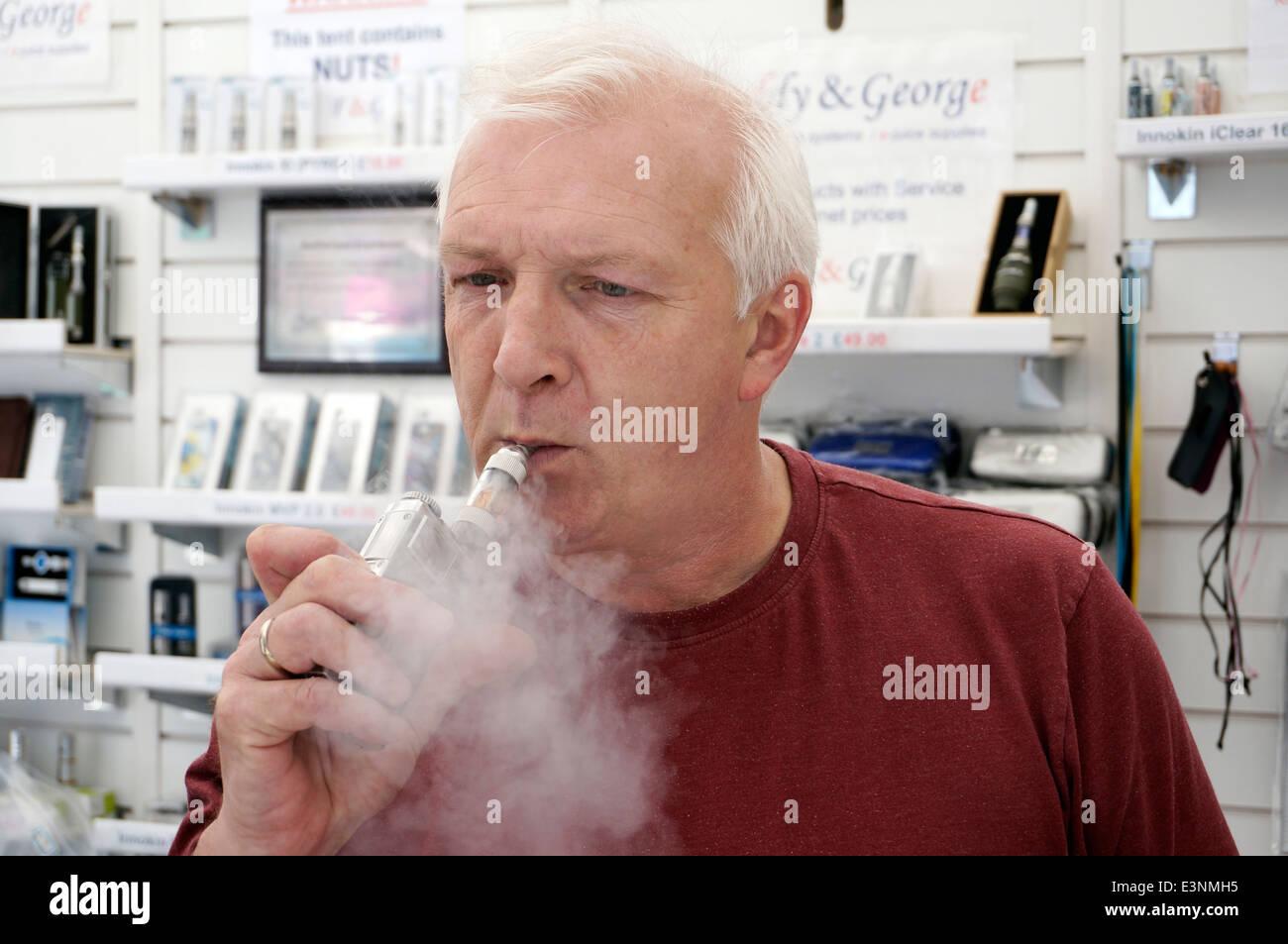 Man smoking an Electronic E Cigarette (e-cigarette) to help stop smoking ordinary tobacco - Stock Image