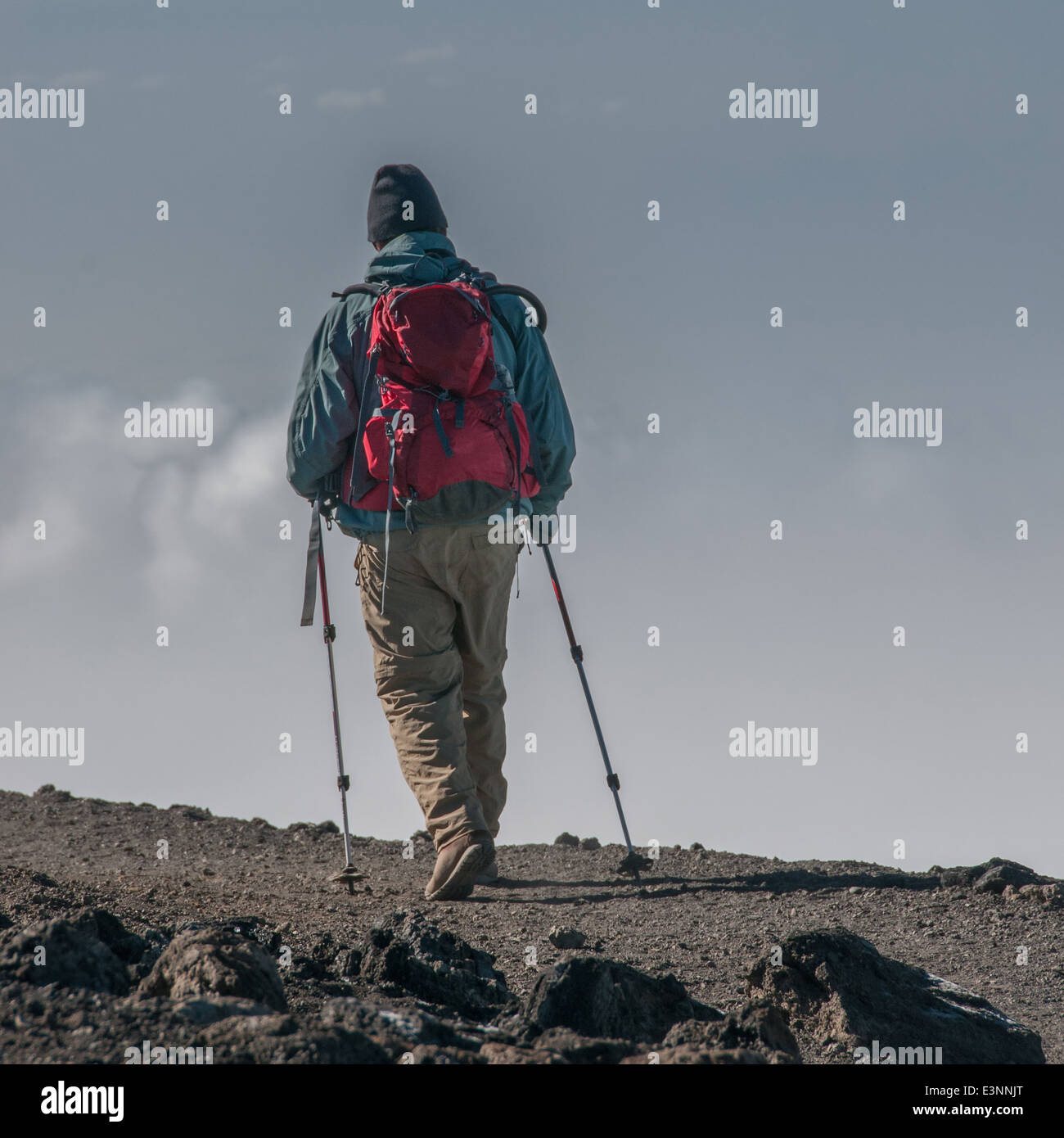 A trekker heading back along the crater rim to Stella Point after successfully summiting Kilimanjaro - Stock Image