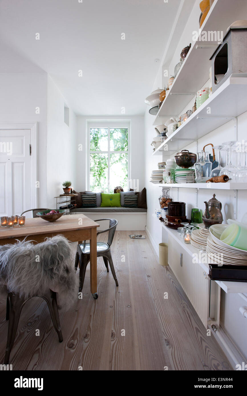 Open plan kitchen with wall shelving and window seat. - Stock Image