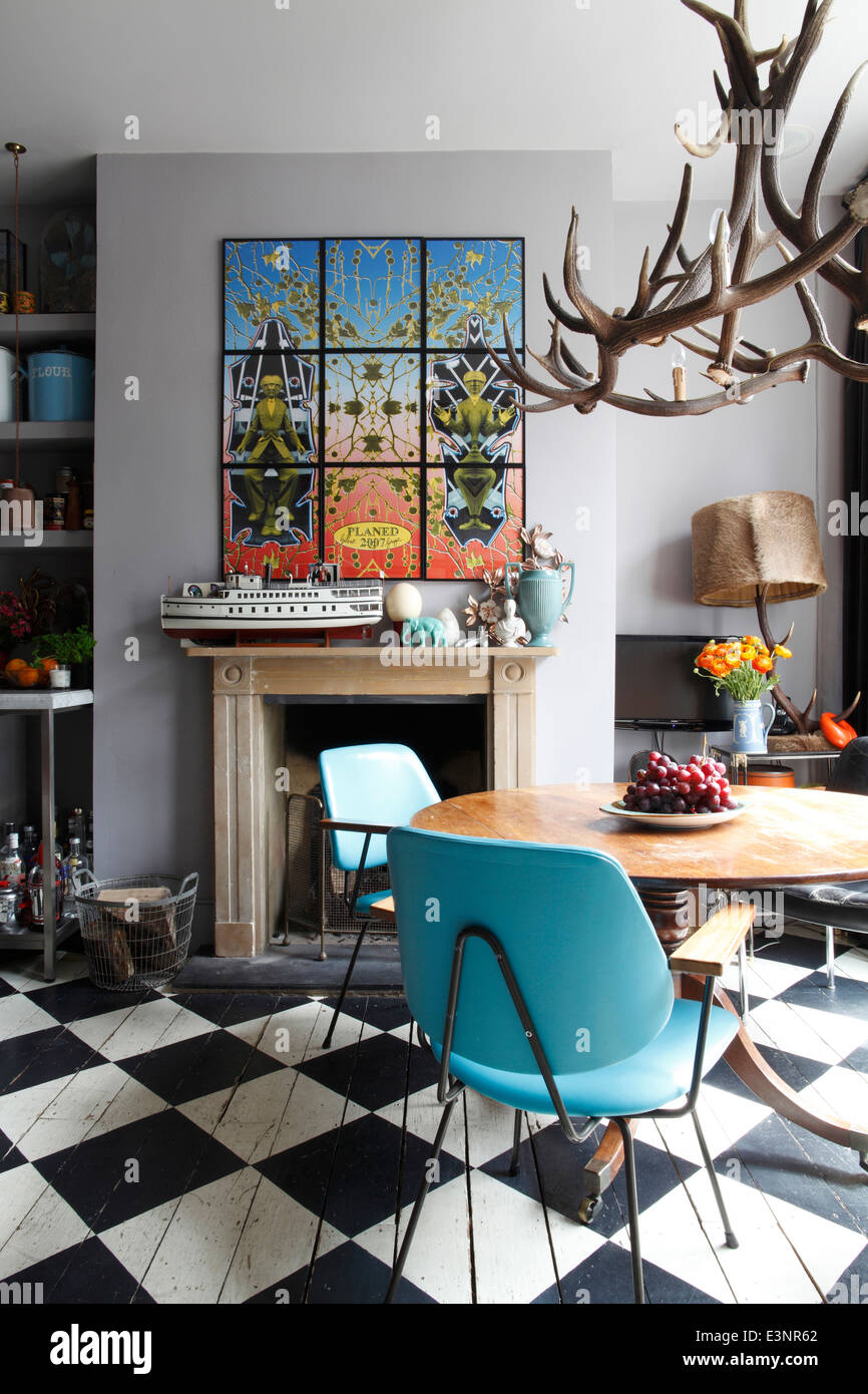 Dining area with painted chequerboard floor, fifties blue leather chairs, antler chandelier & Gilbert & - Stock Image