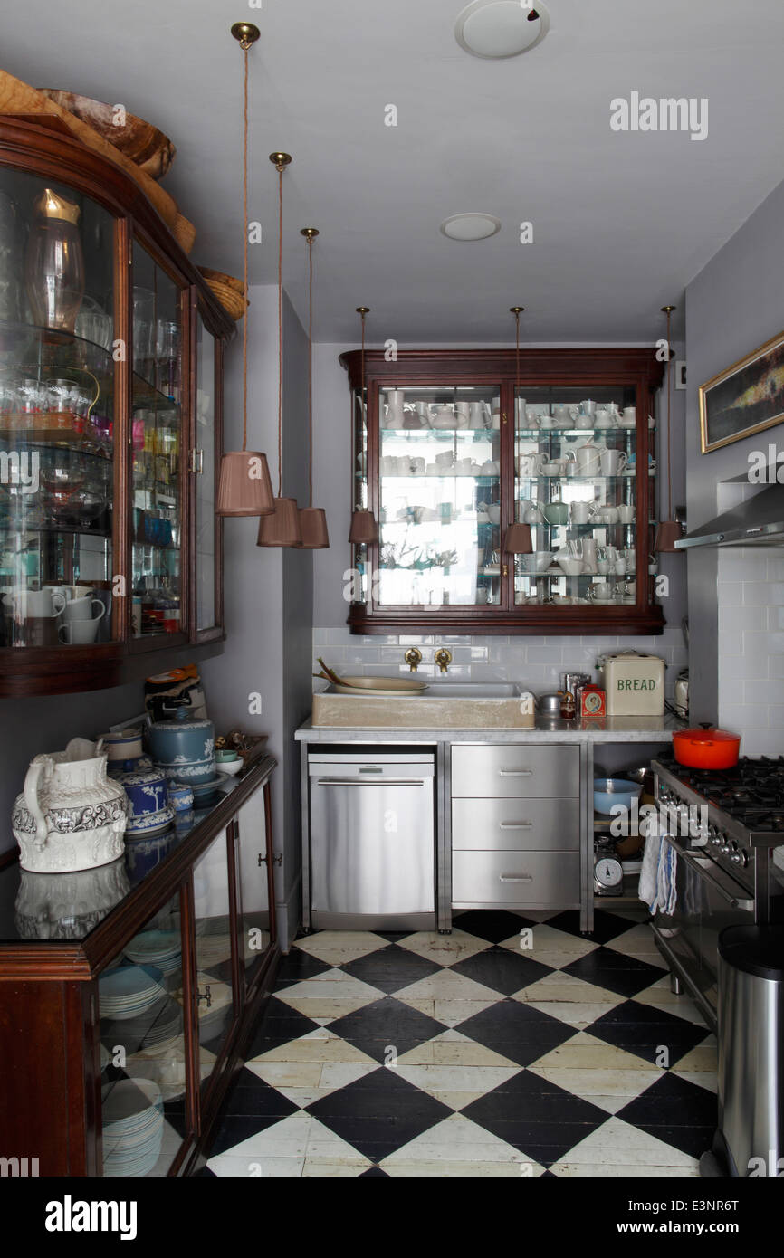 Kitchen with kitchen units from salvaged shopfittings on a black and white chequerboard floor - Stock Image