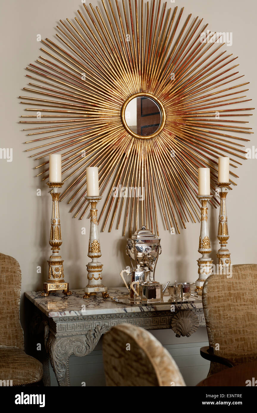 Large gilt sunburst mirror on wall above marble topped side table with gilt candle sticks - Stock Image