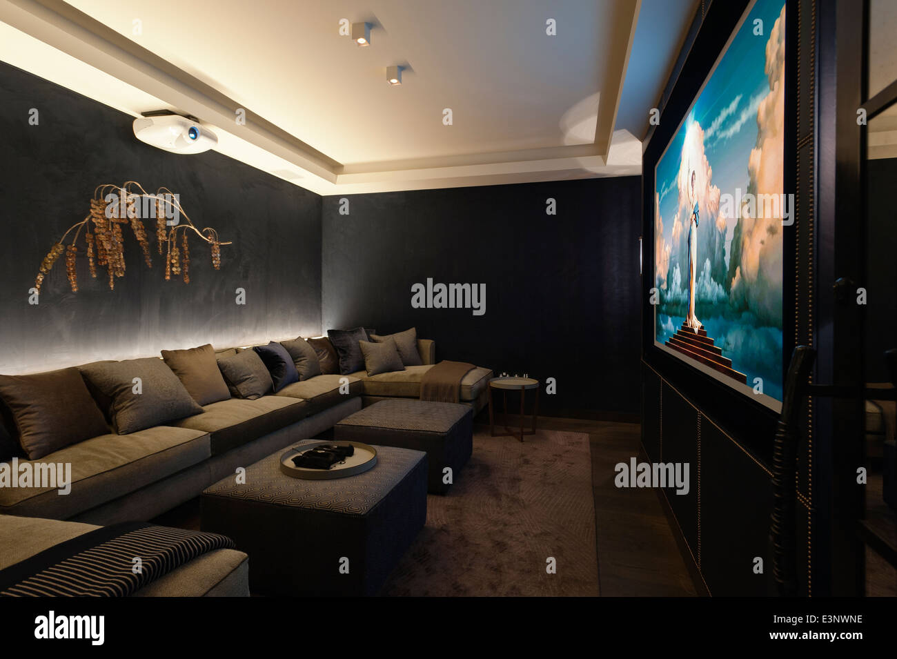 Chic home cinema in dark tones and extended sofa seating - Stock Image