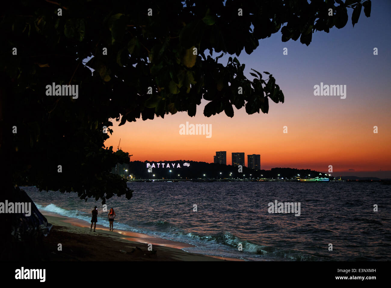 Tourists on the beach during sunset with the Pattaya neon sign in the background in Pattaya, Thailand - Stock Image