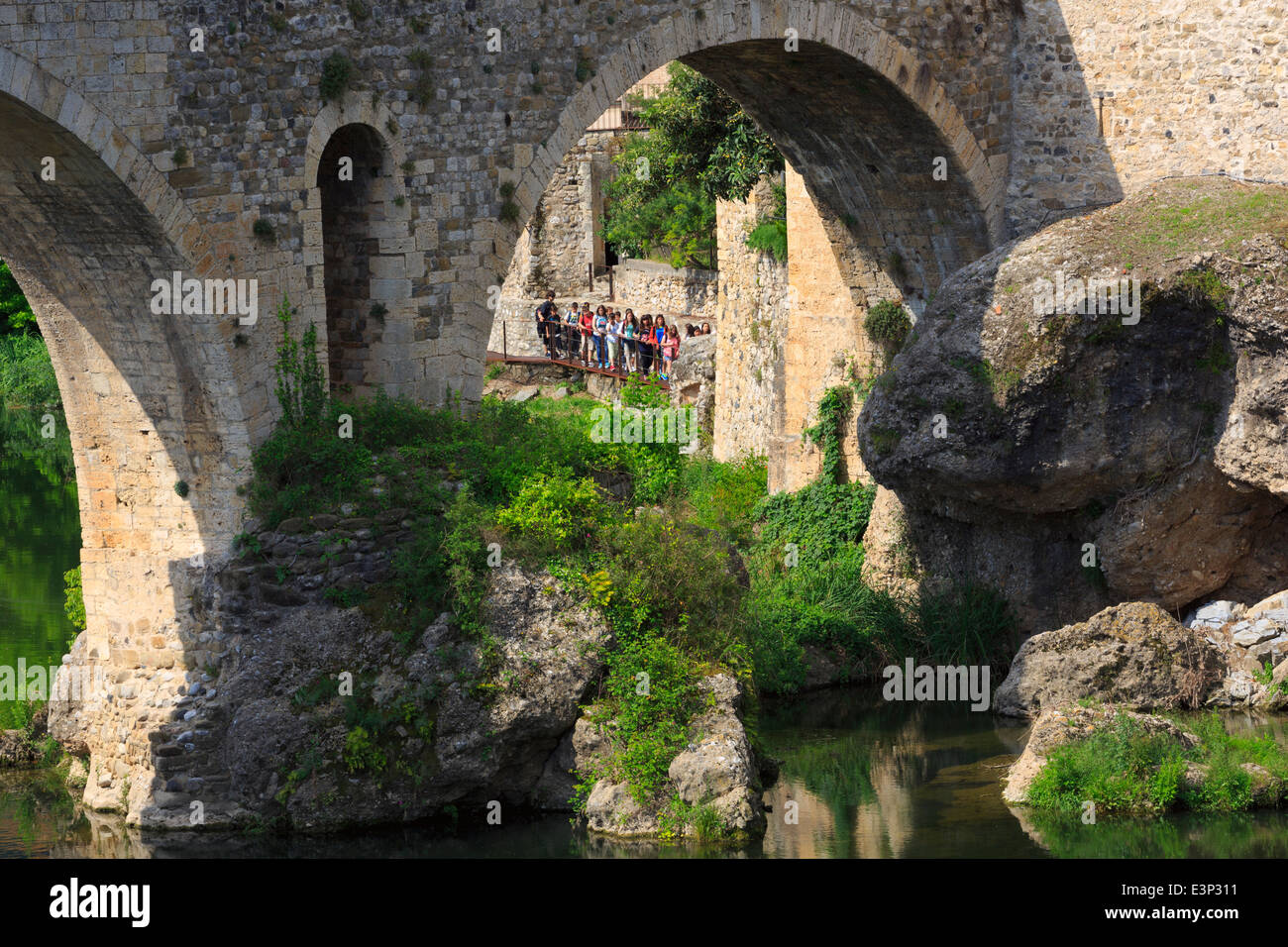 Besalu, Catalonia, Spain. A group of schoolchildren on an outing look up at the construction of the Romanesque bridge. - Stock Image