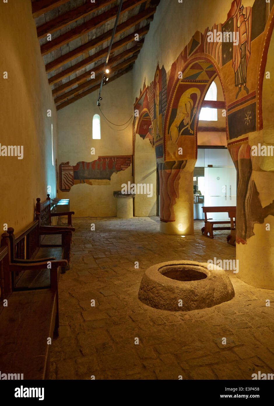 Church of Saint Joan de Boi in the Vall de Boi, Spain. Interior wall paintings and ancient font. - Stock Image