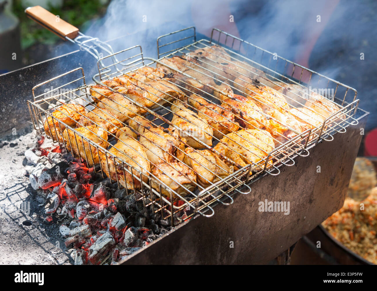 Preparation of chicken meat slices in sauce on fire - Stock Image