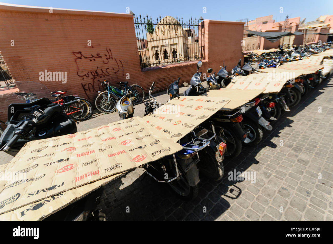 Cardboard placed on the seats of parked motorbikes and scooters to stop the hot sun heating them up, Marrakech, - Stock Image