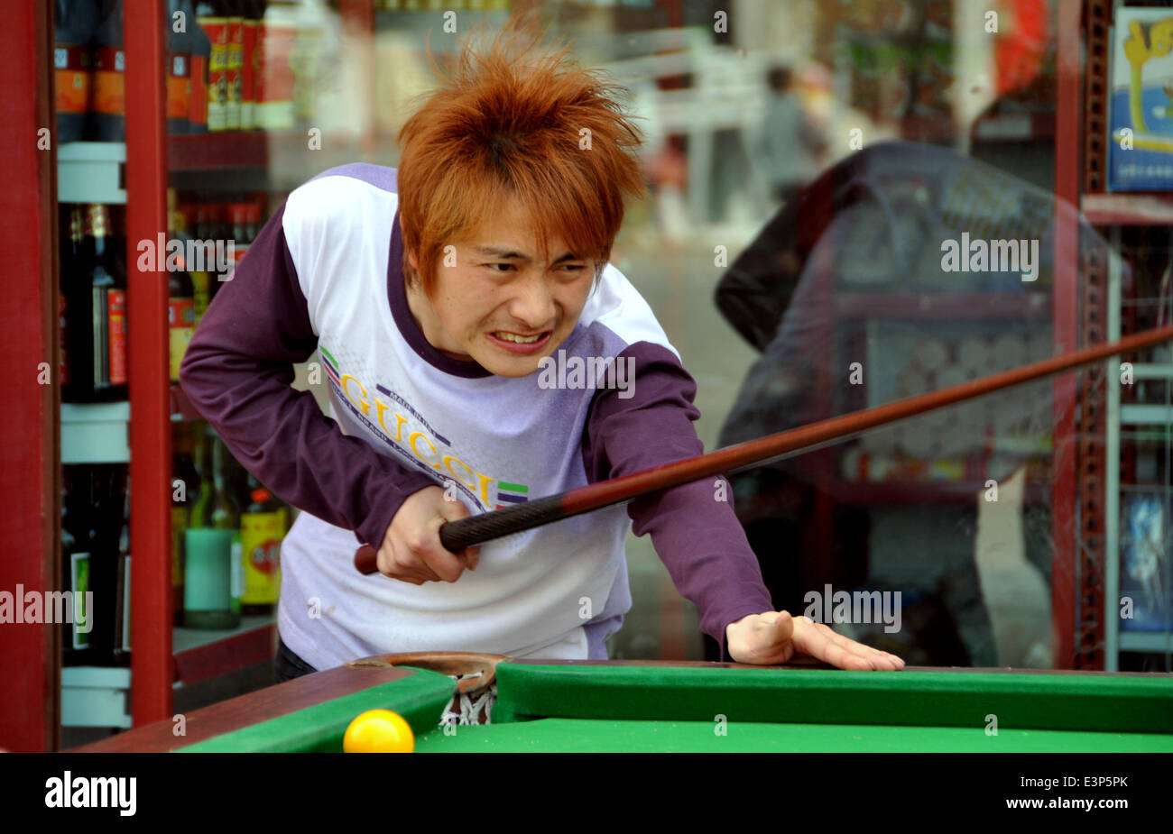PENGZHOU, CHINA: Chinese youth with dyed red hair expresses dismay after missing a shot while playing pool - Stock Image
