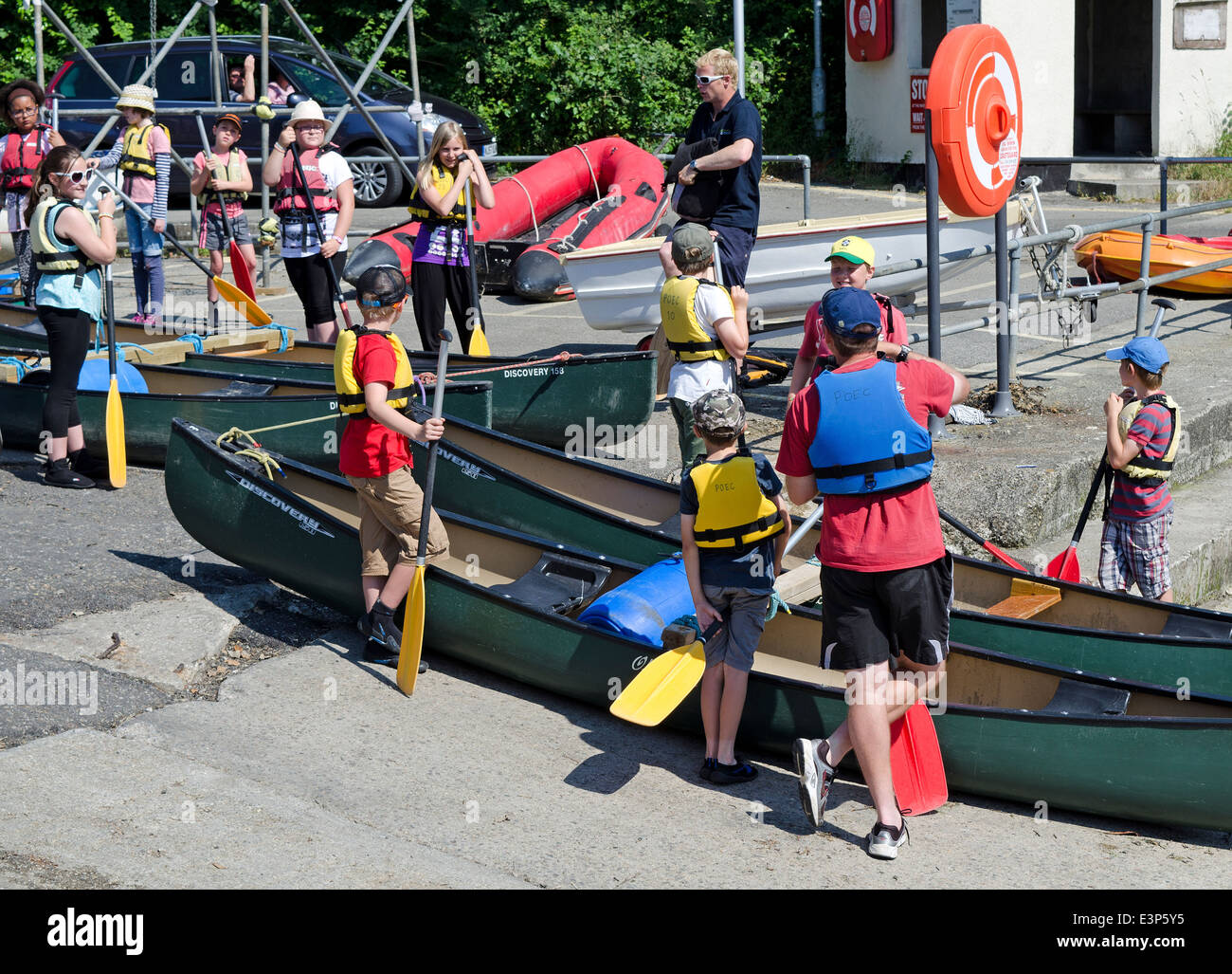 schoolchildren getting ready to canoe on the river fowey in cornwall, uk - Stock Image