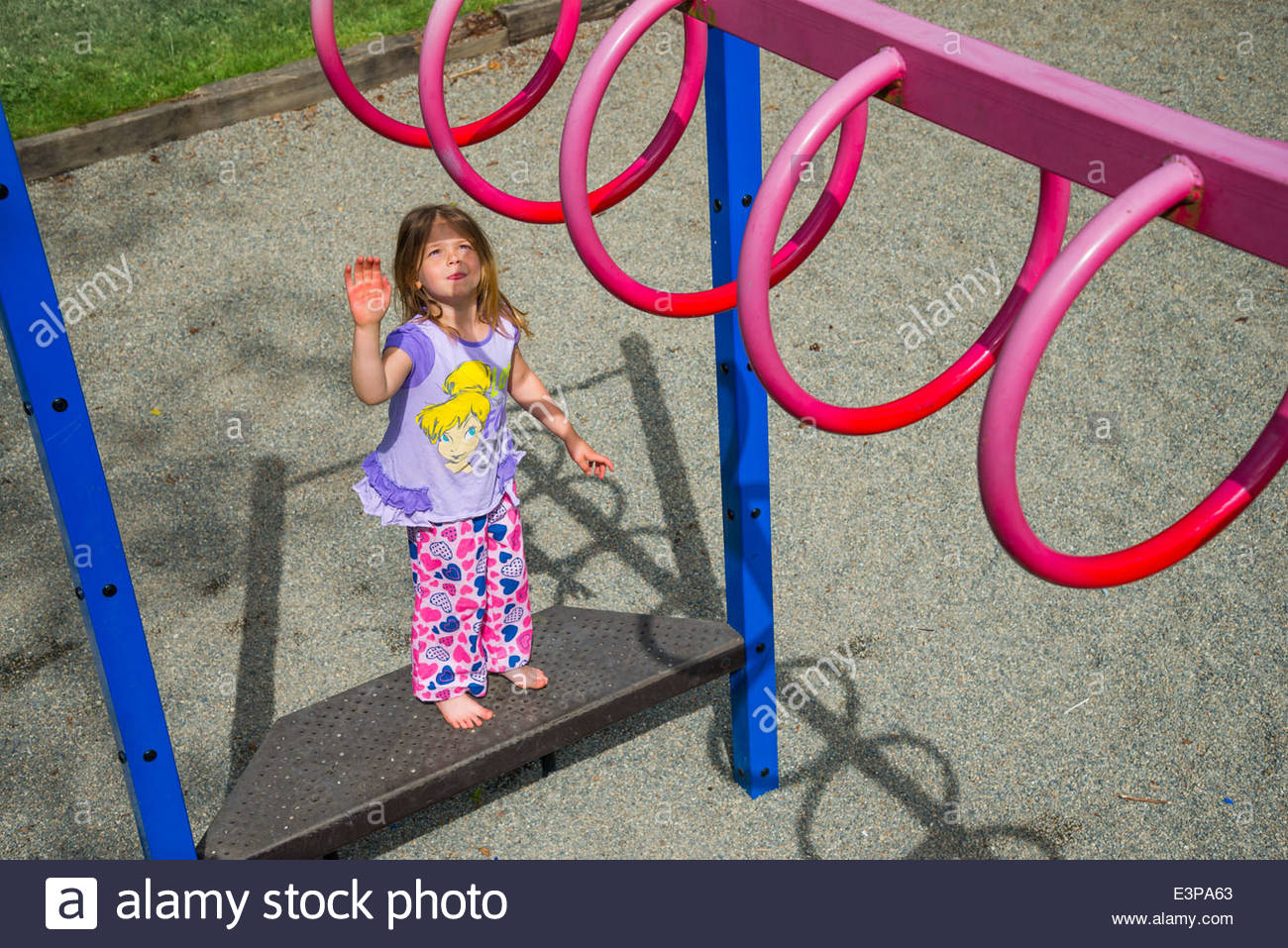 Young girl and playground ring bars. - Stock Image