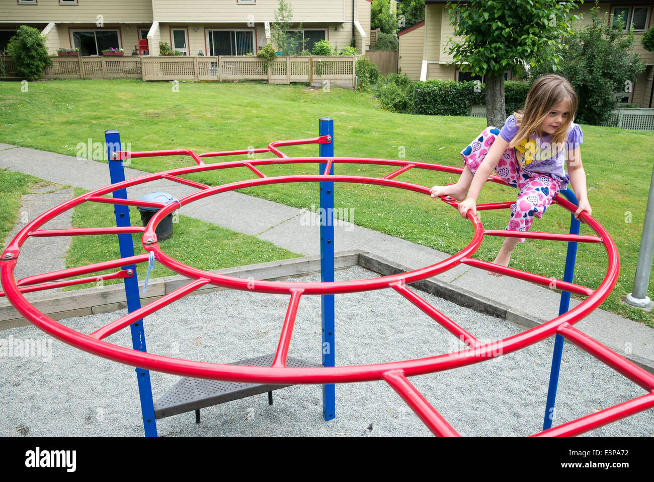 Young girl on playground bars. - Stock Image