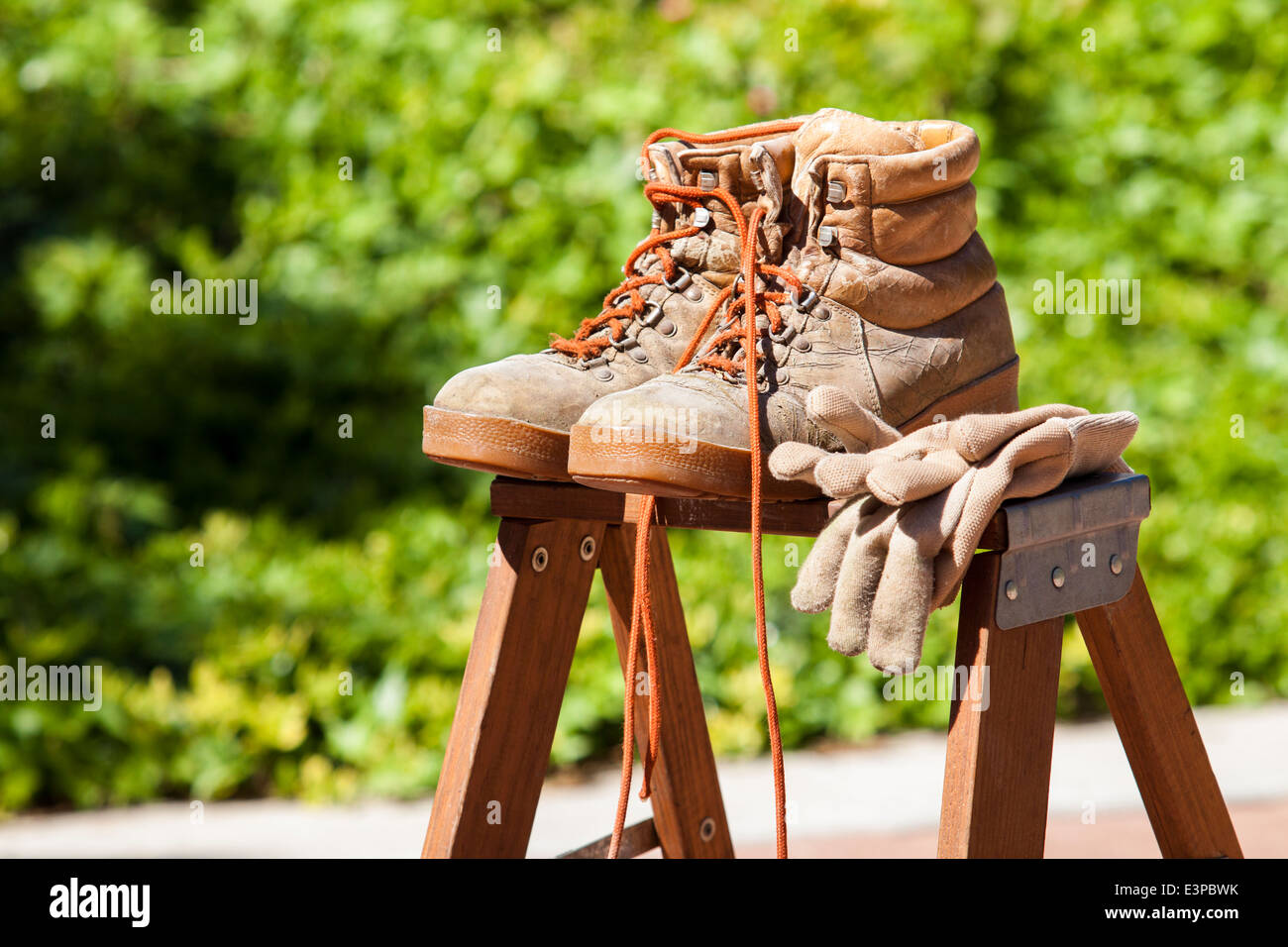 Work boots and gloves on a step ladder - Stock Image
