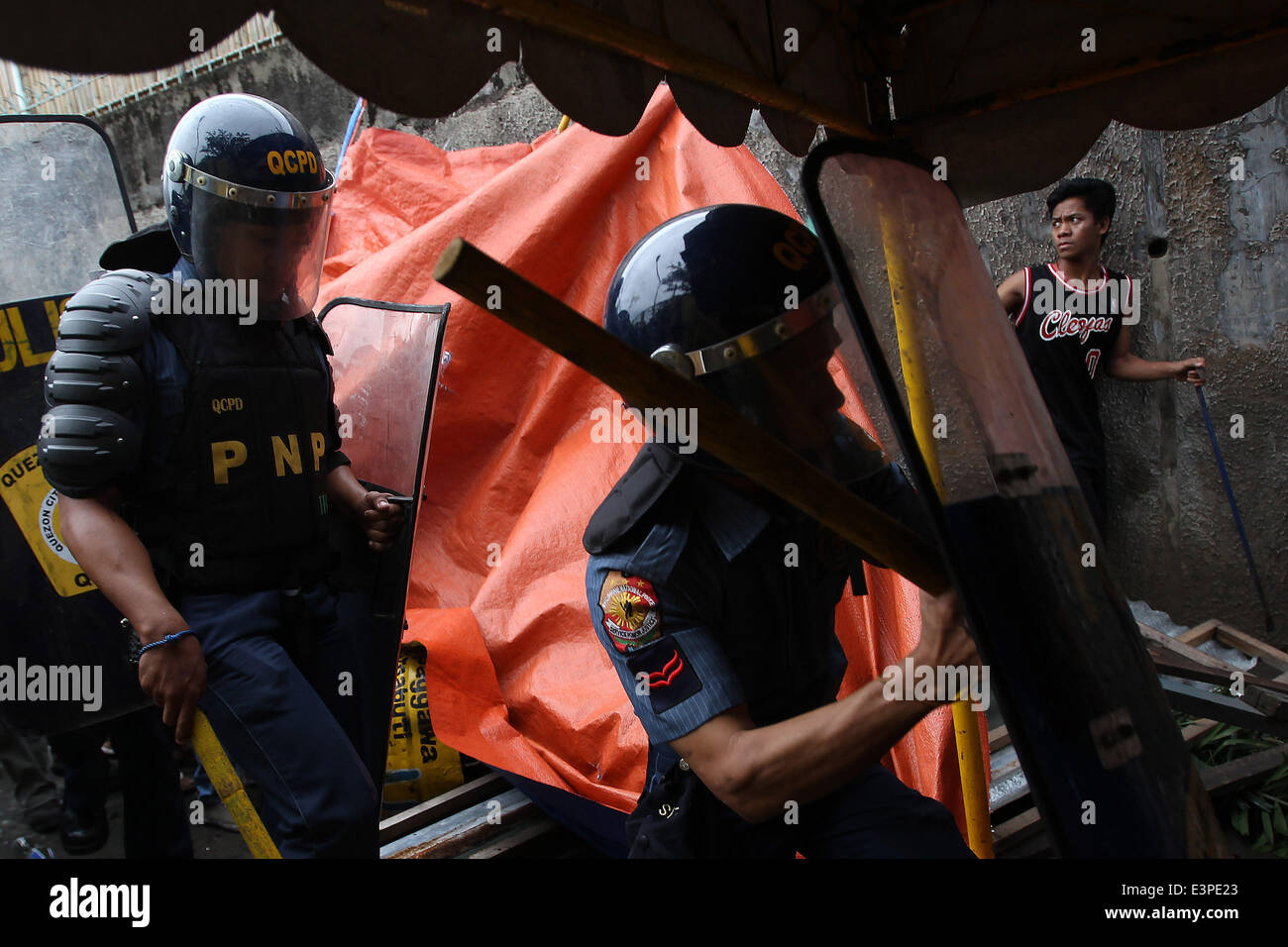 Quezon City, Philippines. 26th June, 2014. Policemen enter a home during the demolition of shanties in Quezon City, - Stock Image