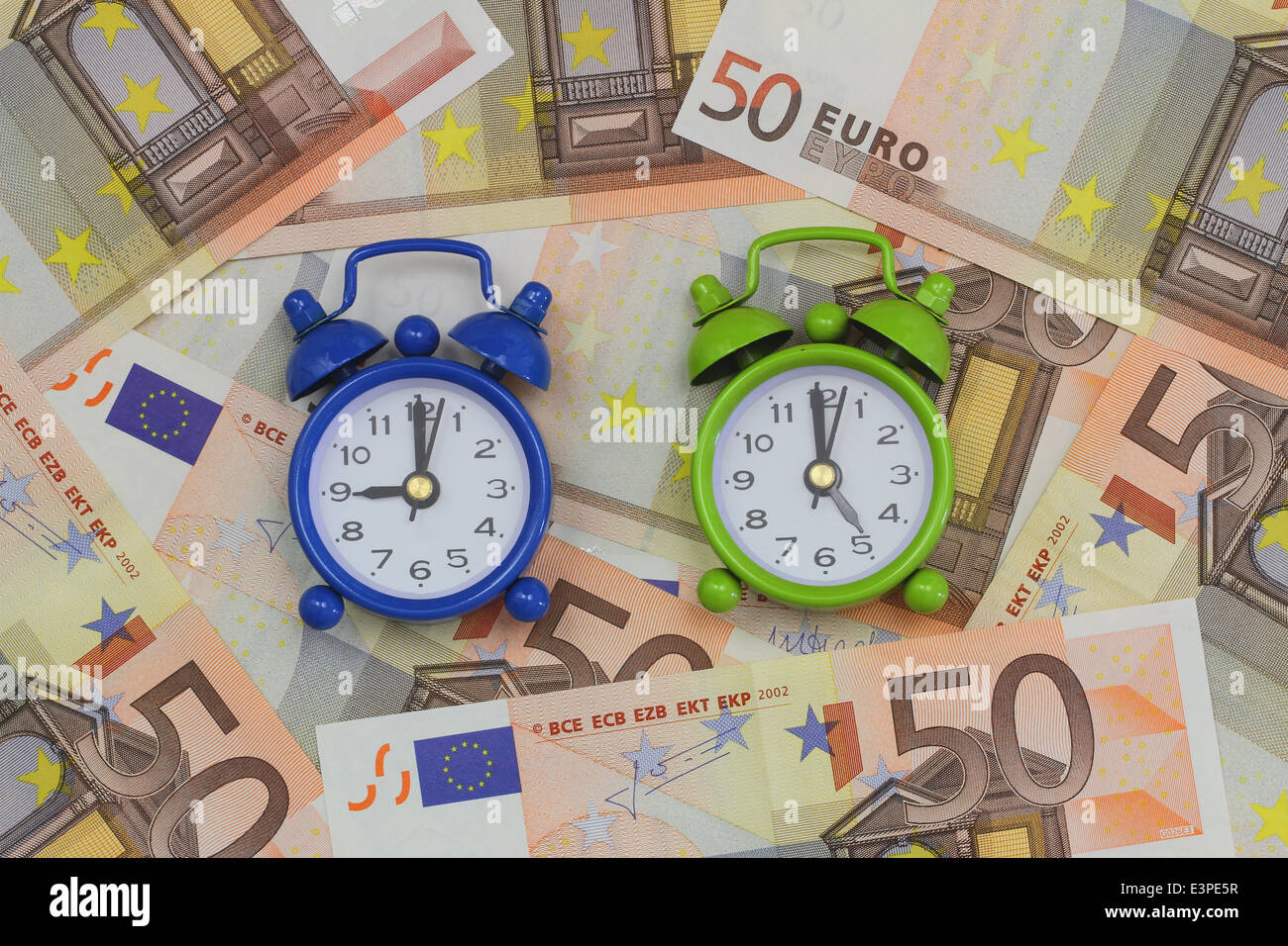Miniature clocks showing nine and five o'clock on banknotes, concept of a nine to five job Stock Photo