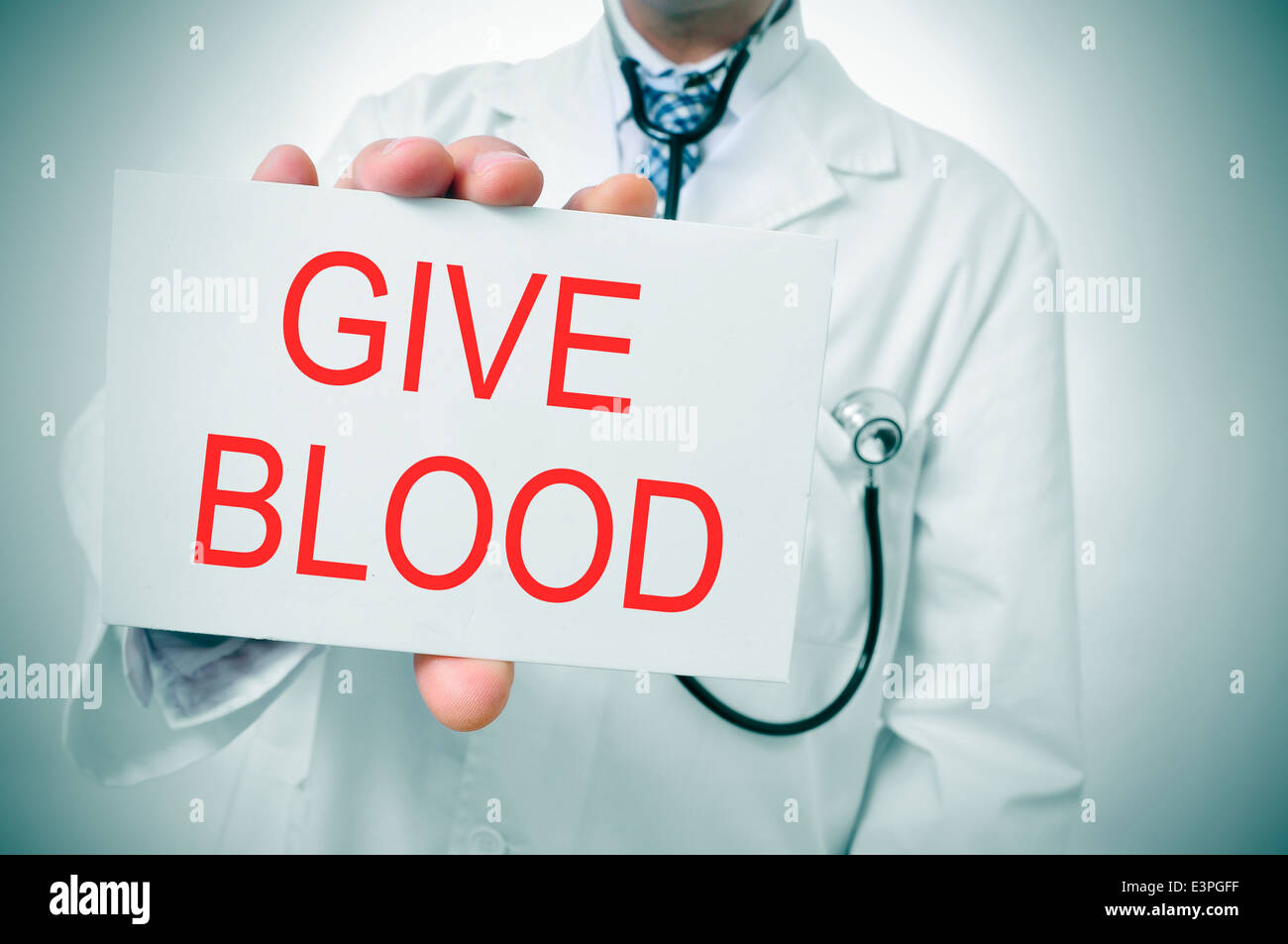 a doctor showing a signboard with the sentence give blood written in it - Stock Image