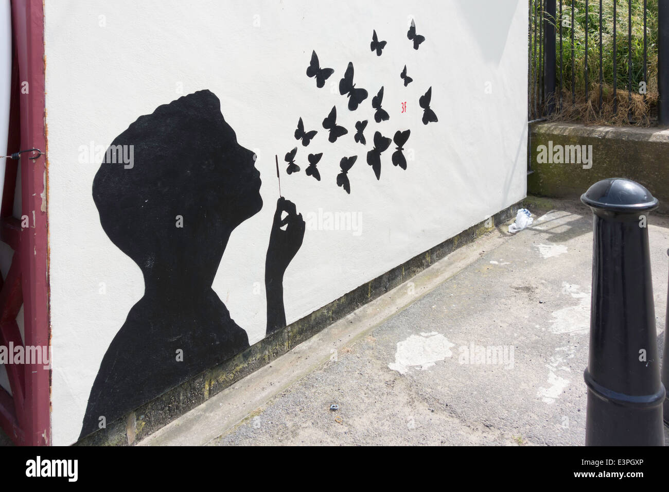 A Graffito of a boy blowing bubbles that are butterflies flying away - Stock Image