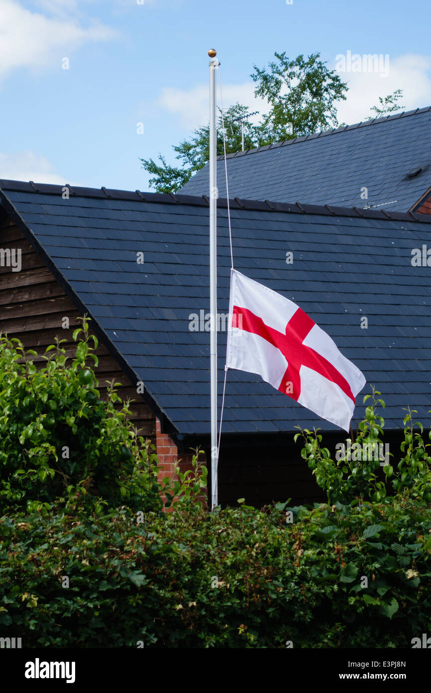 An English flag (the St George's Cross) flies at half mast after England's defeat in the 2014 Football World - Stock Image