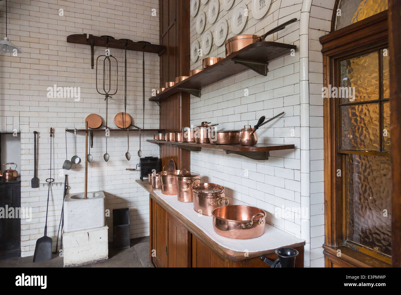 Traditional shiny copper pots, pans and saucepans in old-fashioned white tiled kitchen in Tatton Park, Cheshire - Stock Image