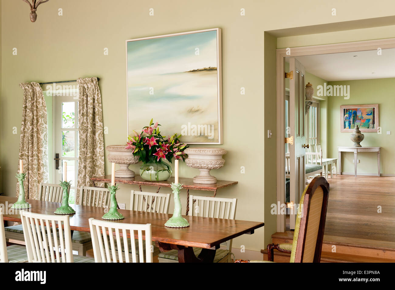 Old French farmhouse table in dining room with Swedish style chairs and green ceramic candle holders. - Stock Image