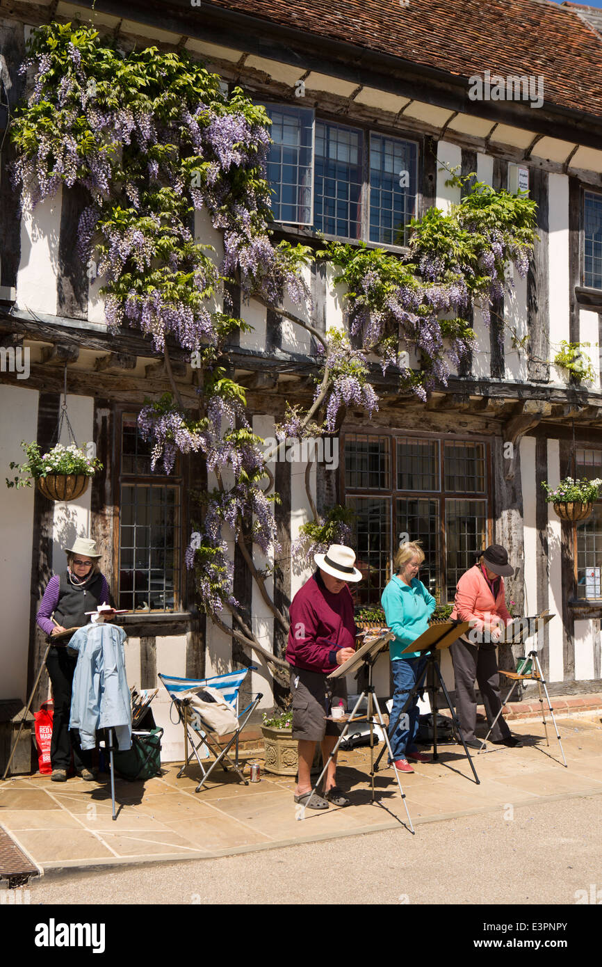 UK England, Suffolk, Lavenham, Market Square, amateur artists painting outside under wisteria in flower - Stock Image