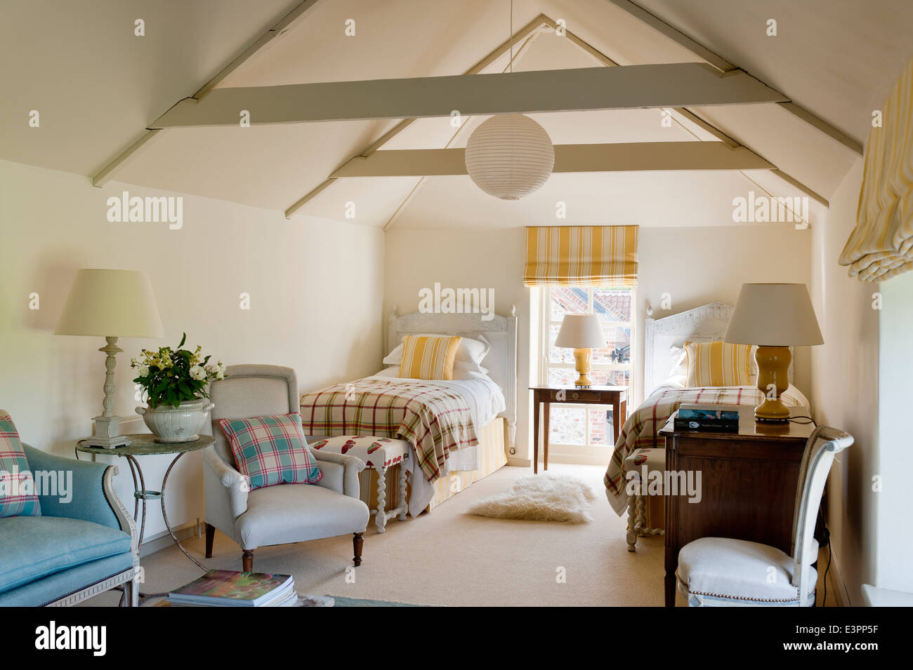Attic twin bedroom with beamed ceiling, yellow striped matching blinds and cushions and blue armchairs - Stock Image