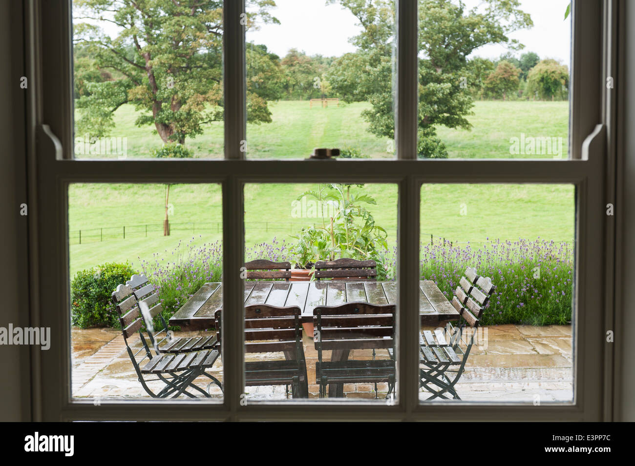 View through paned window out to wet garden terrace with garden furniture - Stock Image
