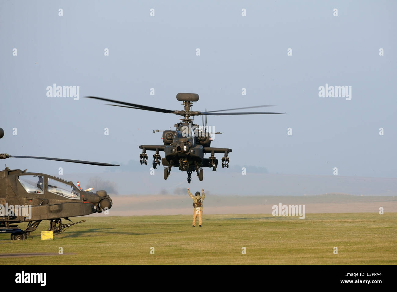 British Army AH-64 marshalled to dispersal at Airfield Camp, Netheravon after pre-deployment training sortie on - Stock Image