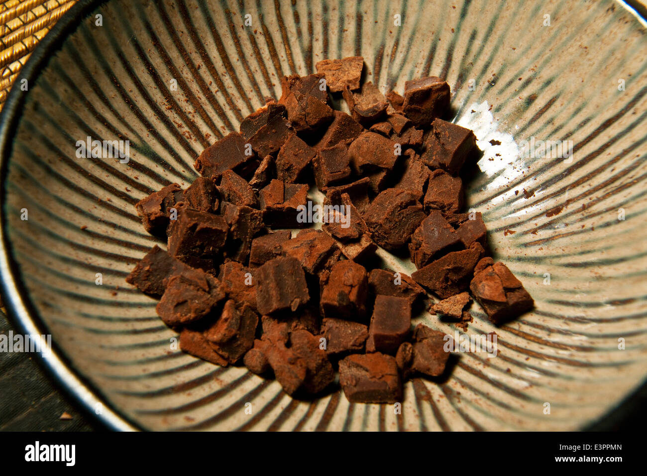 Closeup of rich organic dark chocolate tester in a rustic bowl min tasters. - Stock Image