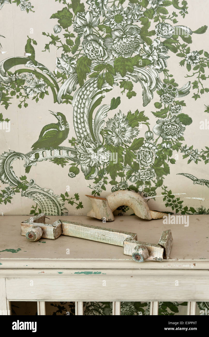 Piece of broken architectural salvage on ledge with patterned wallpaper behind - Stock Image