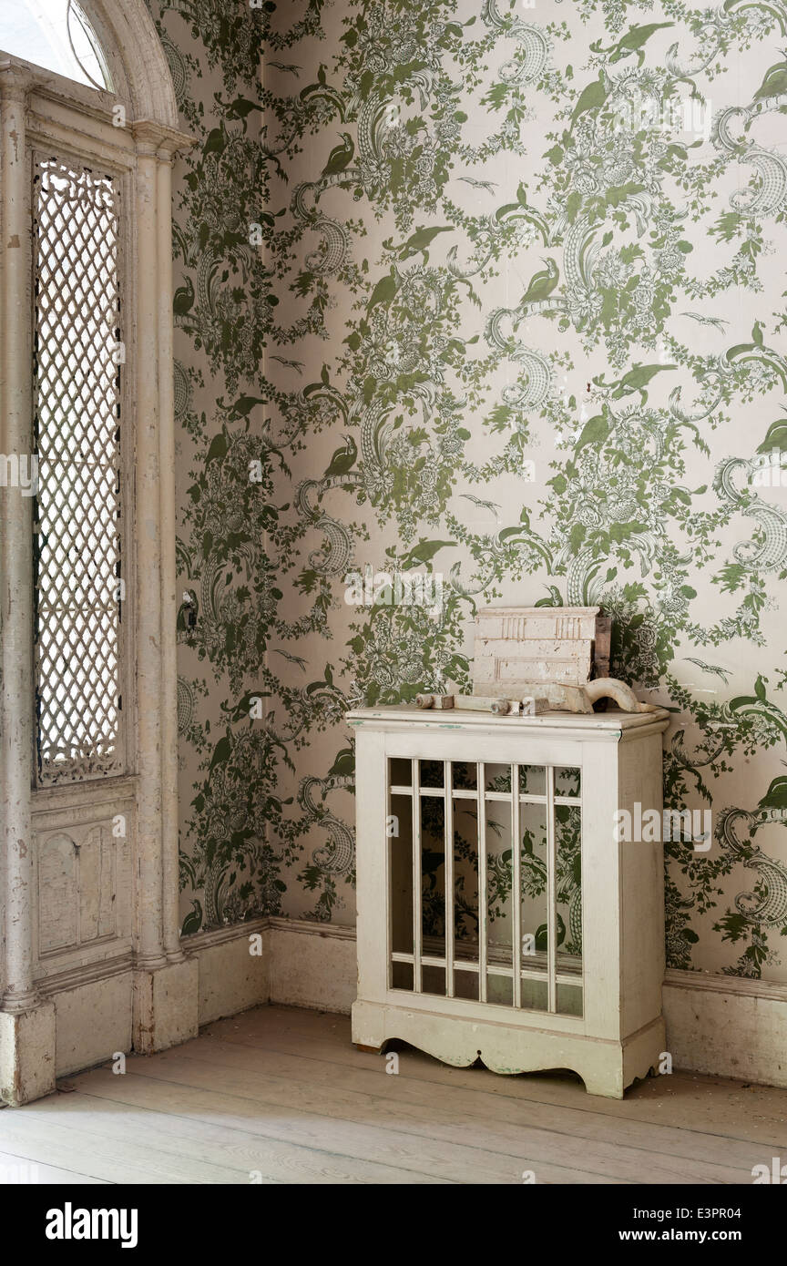 Piece of broken architectural salvage on old radiater cover with patterned wallpaper behind - Stock Image